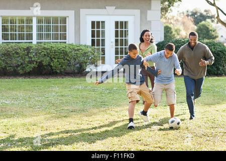 La famiglia che giocano a calcio nel cortile posteriore Foto Stock