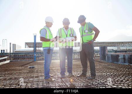 Lavoratori edili parlando sul tondino al sito in costruzione