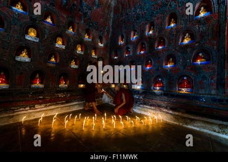 Asian monaci-in-formazione accendendo candele in antico tempio Foto Stock