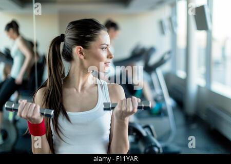 Bella e giovane donna sollevamento pesi in una palestra in piedi accanto a uno specchio Foto Stock