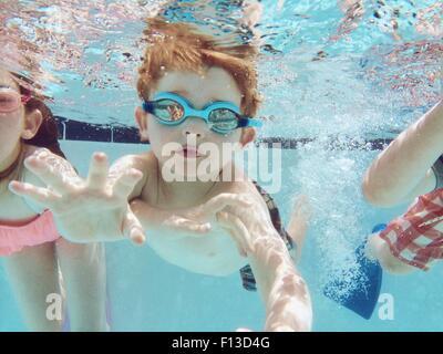 Ritratto di un ragazzo di nuoto sott'acqua con gli amici Foto Stock
