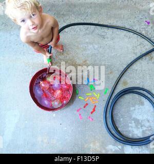 Il Toddler riempire un secchio con acqua Foto Stock