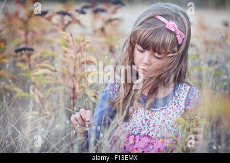 Ragazza che gioca in un campo di fiori Foto Stock