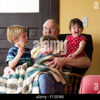 Tre bambini seduti sulle loro nonno lap Foto Stock