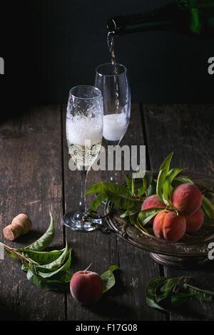 Le pesche sul ramo con champagne Foto Stock