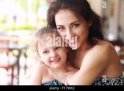 Felice madre bella cuddling la figlia con sorriso in cafe. Closeup ritratto Foto Stock