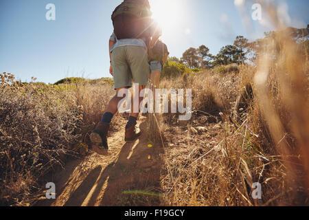 Basso angolo vista di due giovani salita su una montagna. Coppia con un escursione in una giornata di sole. Foto Stock