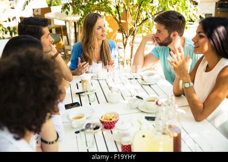 Sorridente giovani amici godendo di pasto in un ristorante esterno Foto Stock