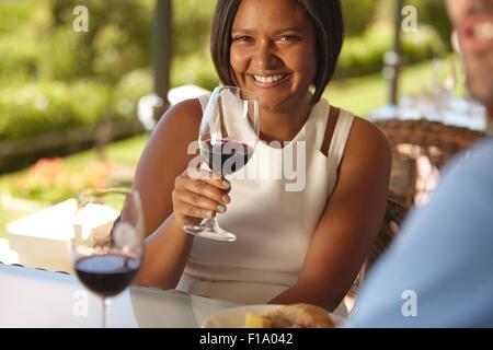 Ritratto di giovane e bella donna seduta a un tavolo in cantina con in mano un bicchiere di vino rosso e sorridente alla fotocamera.