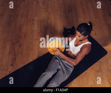 Vista superiore del forte giovane donna facendo allenamento core utilizzando kettlebell peso. Femmina muscolare Foto Stock