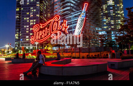 Giovane seduto inondate di luce rossa dal gigante neon di Pepsi Cola segno ,Gantry Plaza del Parco Statale di Long Foto Stock