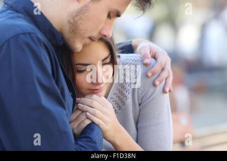 L uomo è consolante il suo triste lutto amico abbracciando la sua in un parco Foto Stock