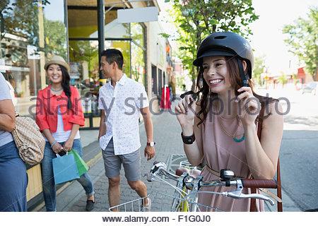 Donna sorridente con bicicletta mettendo sul casco Foto Stock