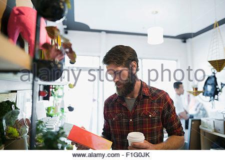 Uomo Barbuto con caffè navigando in negozio Foto Stock
