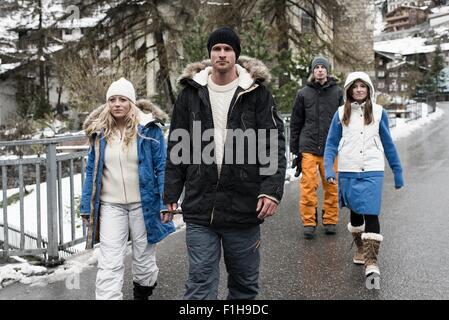 Quattro amici indossando abiti invernali, passeggiate Foto Stock