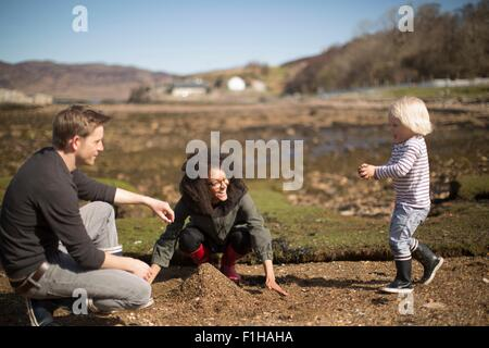 La madre e il padre giocando con il figlio, rendendo pila di suolo Foto Stock