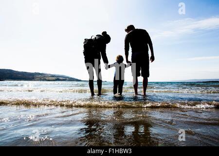 Famiglia tenendo le mani sulla spiaggia, Loch Eishort, Isola di Skye, Ebridi, Scozia Foto Stock