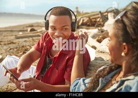 Coppia giovane seduto sulla spiaggia, uomo che indossa le cuffie Foto Stock