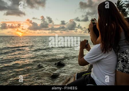 Giovane fotografa sunrise sugli smartphone, Kaaawa beach, Oahu, Hawaii, STATI UNITI D'AMERICA Foto Stock