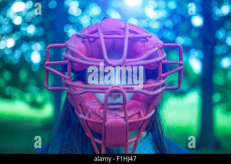 Ritratto di staring ragazza adolescente nel parco rosso da indossare maschera arbitro Foto Stock