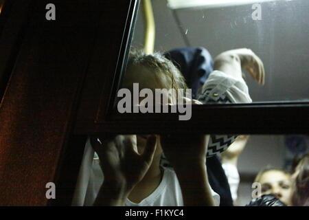 Atene, Grecia. Il 3 settembre 2015. Una bambina guarda fuori dalla finestra del bus che la porterà alla stazione Foto Stock