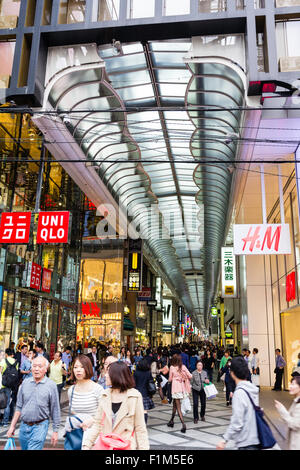 Giappone, Osaka. Guardando lungo Shin Saibashi Suji coperto shopping street, H&M e Uni Qio negozi in primo piano Foto Stock