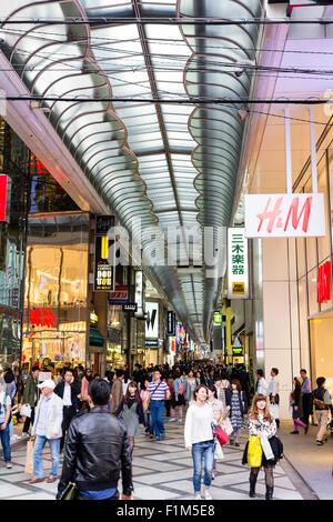 Giappone, Osaka. Guardando lungo Shinsaibashi Suji coperto via dello shopping arcade, con H&M e Uni Qio negozi in Foto Stock