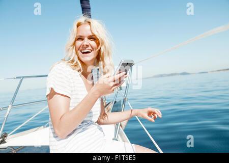 Giovane donna utilizzando smart phone su barca a vela mare Adriatico