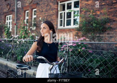 Colpo all'aperto della giovane donna a piedi lungo la strada con una bicicletta che guarda lontano. Donna con la Foto Stock