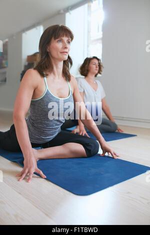 Femmina istruttore di fitness a yoga classe a pigeon pongono sul suo materassino yoga in palestra. Le donne a lezione Foto Stock