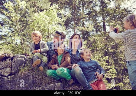 Ragazzo giovane tenendo fotografia di famiglia, nella foresta
