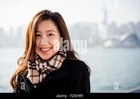 Ritratto di giovane donna indossa foulard controllato di fronte acqua, guardando alla fotocamera a sorridere Foto Stock