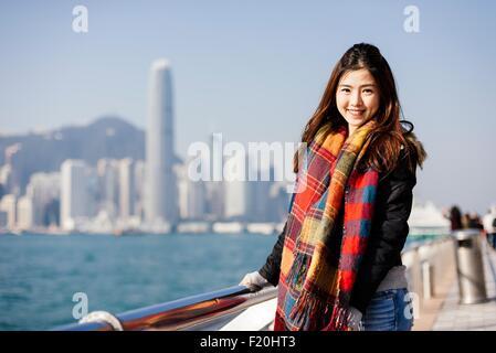 Ritratto di giovane donna che indossa controllato sciarpa e giacca di pelle, guardando la fotocamera Foto Stock