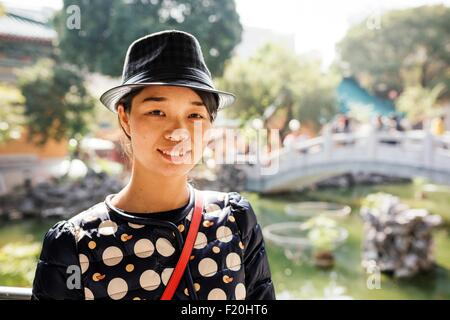 Ritratto di giovane donna che indossa il cappello in parte anteriore del giardino cinese bridge, guardando la fotocamera