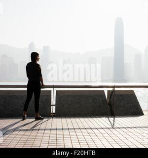 Stagliano vista laterale della giovane donna in piedi che guarda fuori acqua oltre a skyline di Hong Kong, Cina Foto Stock
