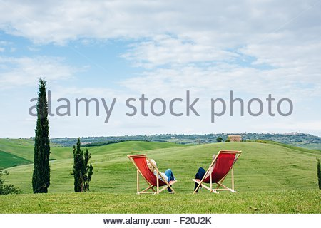 Vista posteriore di due femmina matura amici seduti sulla rossa di sedie a sdraio, Toscana, Italia Foto Stock