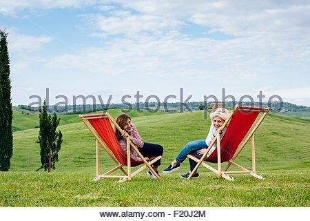 Ritratto di due femmina matura amici seduti sulla rossa di sedie a sdraio, Toscana, Italia Foto Stock