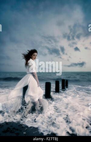 Una ragazza in un abito bianco è seduto su un palo di legno in mare Foto Stock