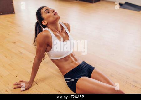 Ritratto di donna stanchi di riposo dopo l'allenamento. Stanco ed esausto atleta donna seduta sul pavimento a palestra. Foto Stock