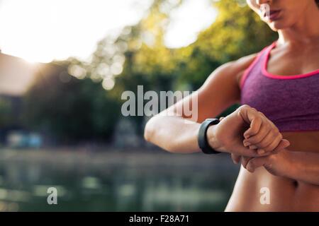 La donna con l'impostazione del fitness orologio smart per l'esecuzione. Sportive controllo guarda il dispositivo.