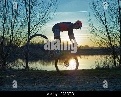 Uomo maturo fare acrobazie in mountain bike durante il tramonto, Baviera, Germania Foto Stock