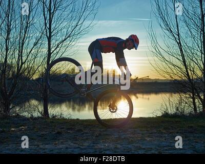 Uomo maturo fare acrobazie in mountain bike durante il tramonto, Baviera, Germania Foto Stock