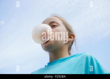 Ragazza soffiando la gomma da masticare bolla, Baviera, Germania Foto Stock
