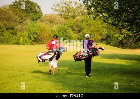 Due uomini che trasportano le sacche da golf a piedi attraverso il corso su un soleggiato, tarda primavera del pomeriggio Foto Stock