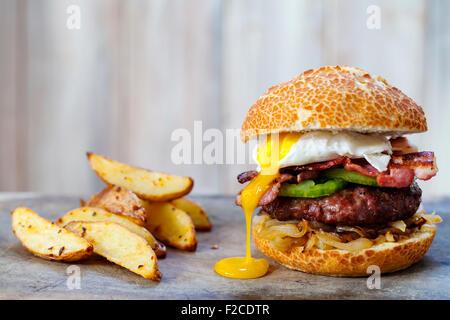 Hamburger di manzo con pancetta e uova in camicia Foto Stock