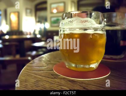 Un bicchiere di birra dorata Foto Stock