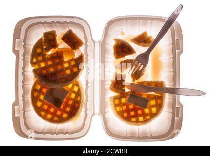 Guardando dritto verso il basso sulle cialde con il burro e lo sciroppo in un contenitore di plastica con una forchetta Foto Stock