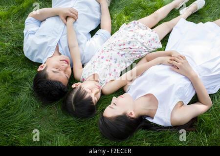 Felice famiglia giovane sdraiati sull'erba Foto Stock