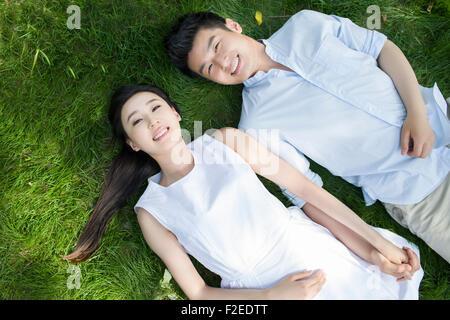 Felice coppia giovane sdraiato sull'erba Foto Stock
