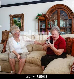 Due senior caucasica donne, sorelle, capire come utilizzare un Kindle fuoco. Stati Uniti d'America. Foto Stock